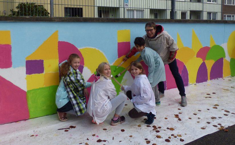 Schulmauer der Grundschule Annastraße leuchtet in bunten Farben